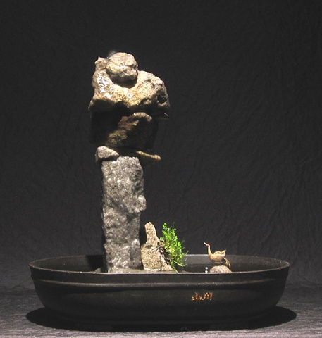 stone inuksuk tower with waterfall and leptinella plant