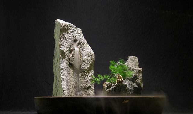zen indoor fountain rock sculpture with plant and chinese figurine