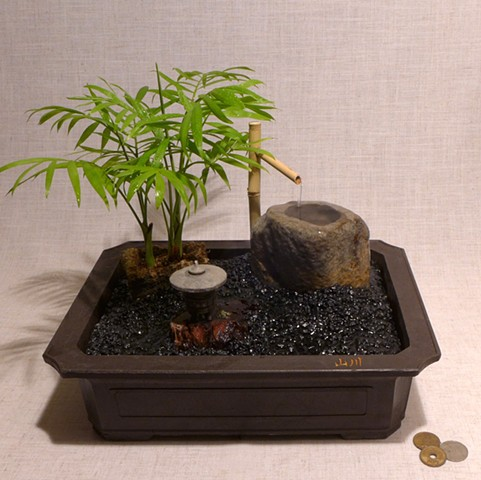 tabletop fountain garden with Neanthe Bella Palm, Malaysian driftwood, cast stone lantern, brass miniature
