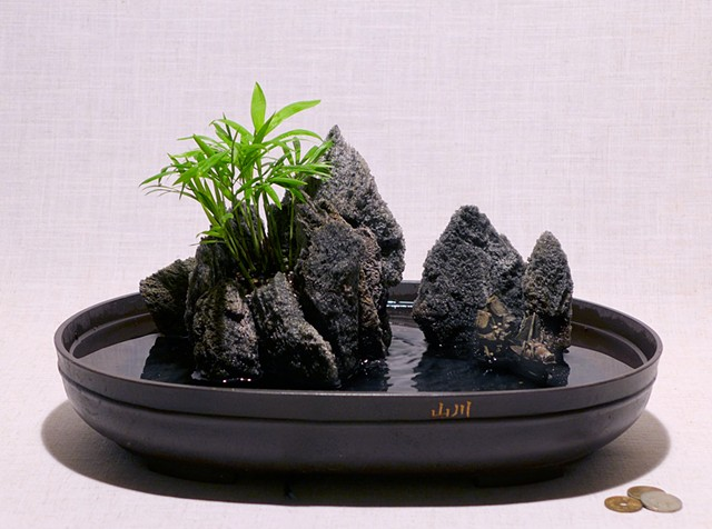 Asian featherock fountain with mudman miniatures and Neanthe Bella palm