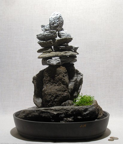 Sonw-capped inuksuk fountain with dwarf plants