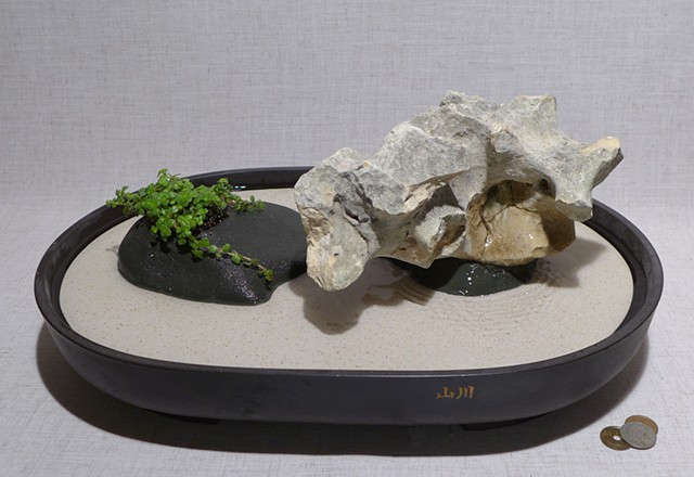 tabletop fountain with limestone, pump, and live plant