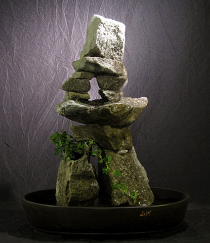 inuksuk rock sculpture with fountain and plant