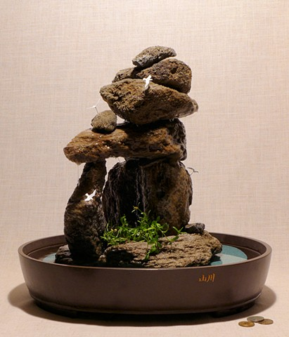 inuksuk fountain with miniature birds and plants