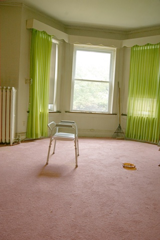 a desolate room that's occupant has moved out or died with a commode chair and ashtray remaining by lucy mueller