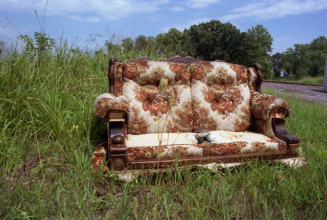 Abandoned orange and brown floral patterned couch abandoned by a railroad track by Lucy Mueller