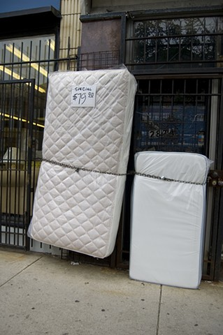mattresses chained as if escaping in front of a city store photographed by Lucy Mueller Photography