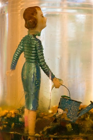 doll with big head holding a watering can under water and seen through glass photographed by Lucy Mueller Photography