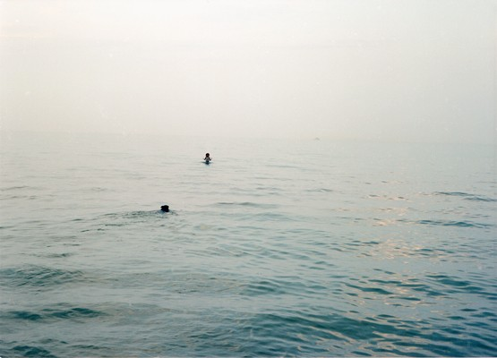 Lake Michigan on an overcast day with a dog and girl swimming in the vast lake photographed by Lucy Mueller