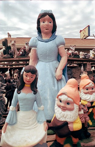 A Snow White concrete lawn sculpture with  a deformed unfinished mouth stands with her dwarfs in Mitchell, South Dakota photographed by lucy mueller