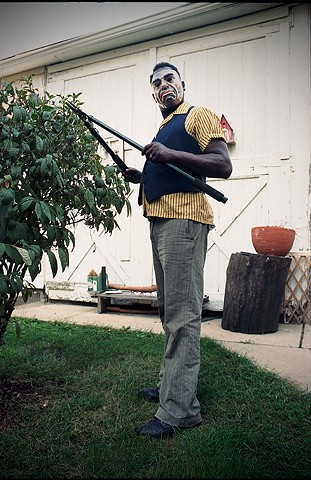 black middle aged man in scary mask that makes him look like a white man is pruning a shrub in his yard photographed by Lucy Mueller Photography