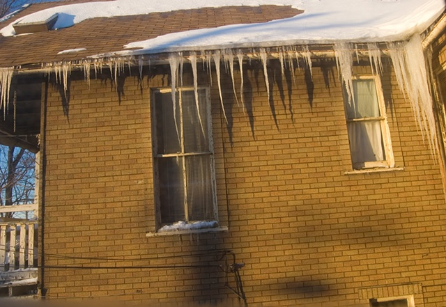 large icicles hang from the upstairs of an old house that is bathed in afternoon sun photographed by Lucy Mueller