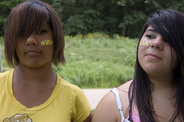 Two pubescent girls with colorful band aids on opposite cheeks by Lucy Mueller