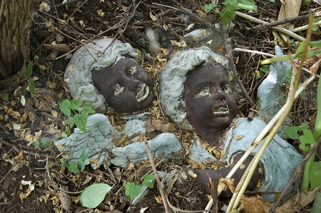Plaster angels painted with black faces are buried in  overgrowth photographed by Lucy mueller