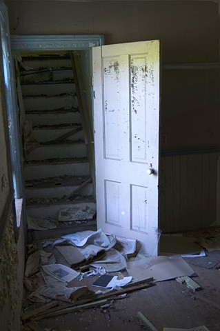 A door with peeling paint leading to a darkened staircase in an abandoned house by Lucy mueller