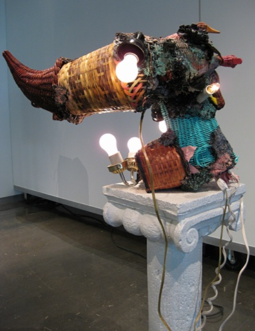 Title/Materials: Wicker Baskets and Cornucopia, Light Fixtures, Light Bulbs, Electrical Receptacles, Electrical Wiring, Plaster Column, Paint, Sawdust. Wood Glue, Extension Cord