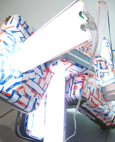Detail Title/Materials: Suitcases, Fluorescent Fixtures, Fluorescent Bulbs, Name Badge Stickers, Electrical Receptacles, Electrical Wiring and Box