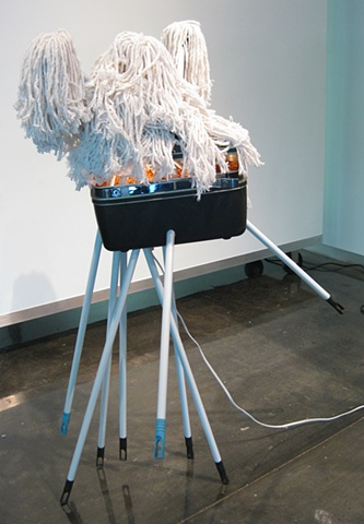 Title/Materials: Mops, Makeup Case, Artificial Flowers, Light Fixture, Light Bulb, Paint, Sawdust, Wood Glue
