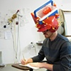 Title/Materials: Igloo Cooler, Baseball Helmet, Ketchup Bottles, Corncob Holders, Plastic Bathroom Cups  Worn as hat