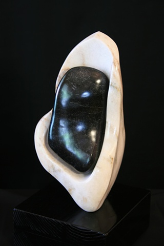 This is a modern contemporary stone sculpture of a seed pod that contains a very ripe seed by Denis A. Yanashot