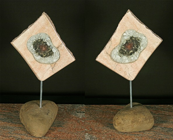 This mixed media sculpture consists of an open pink marble slab filled with glass shards and light sensitive frit encased in clear epoxy resin.  The form is suspended by a pin on a natural sandstone base.