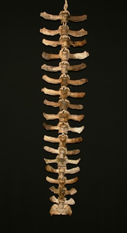 This is a modern contemporary mixed media sculpture of a large rhythmic vertebral column by Denis A. Yanashot
