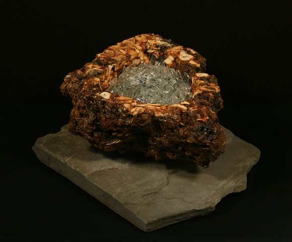 "This mixed media sculpture of the ""geode series"" consists of a carved anthracite burnt culm mass, adhesive, polyurethane and clear glass shards to create a geode-like form that rests on a bluestone base."