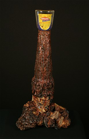 Leak Proof is a mixed media sculpture by Scranton, Pennsylvania sculptor Denis A. Yanashot. This sculpture is composed of defunct anthracite coal waste (burnt culm clumps), acrylic paint, epoxy resin, D size Flashlight battery, mica powders..