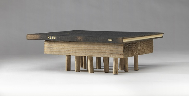 A book about the artist Paul Klee rests on a wooden block suported by numerous small legs.