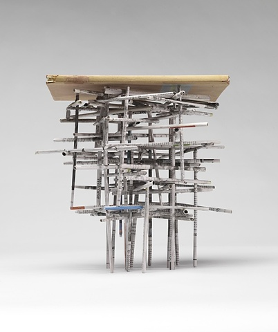 A sculpture of newspaper sticks supports a book lying on top.