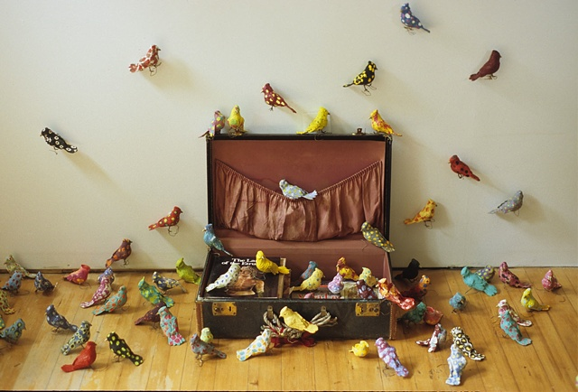 Installation of birds flying out of a suitcase