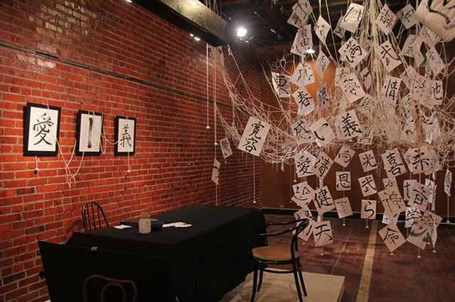 installation art with Japanese calligraphy and threads