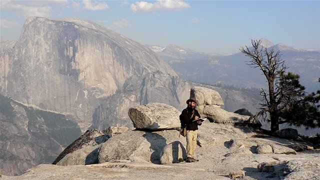 sketching on top of North Dome,  Half Dome visible across the valley Yosemite National Park CA