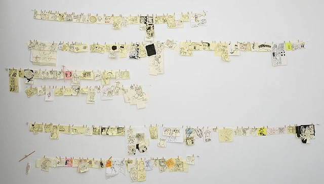 Sumi ink on sticky notes and paper scraps hung on a line.