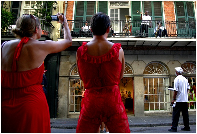 Participants of The Red Dress Run listen to music being performed on a balcony on Royal Street Dirty Linen Night.