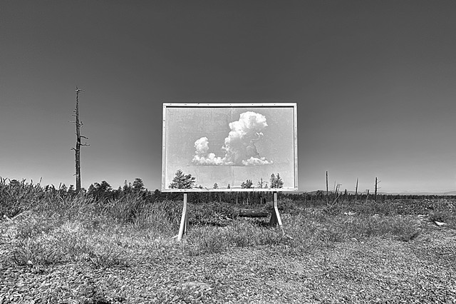 A black and white image of a billboard with a cloud placed in the high desert