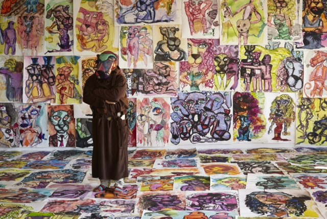 Bjarne in the Pink Panther mask in a room of his paintings.