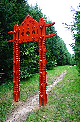 Portal mediates the junction between a formal path and the wild woods beyond.