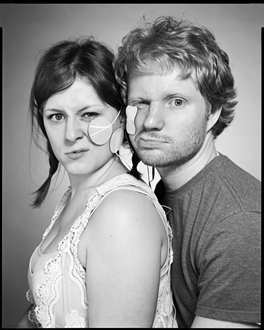 This is a photograph of a couple whose faces are being partially electrically stimulated by a trancutanious muscles stimulator for the photo series 'Sing the Body Electric' by artist Stephen Takacs