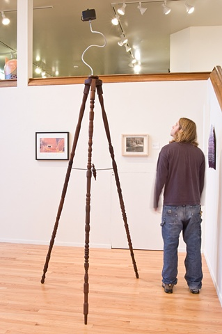 A digital photograph by Columbus Ohio artist and OCAC alumni Stephen Takacs that depicts a large walnut tripod with a camera on top.