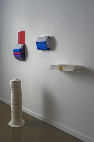 An arrangement of four small works, all made from stacking paper.