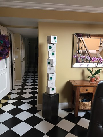 Green totem installed in a room with checkerboard floors; an orchid nearby