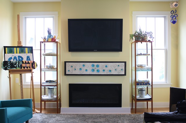 Wall piece with blue glass, mounted in a living room between the TV and the fireplace