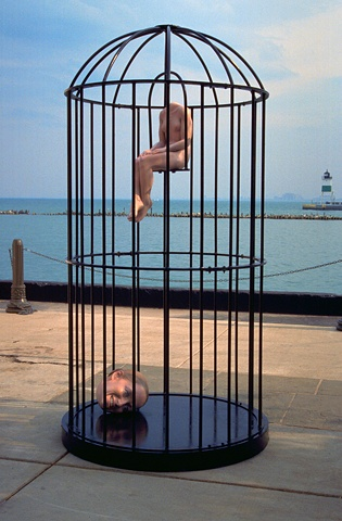 figurative polychrome sculpture of small body and large head in large steel bird-cage at Pier Walk Chicago