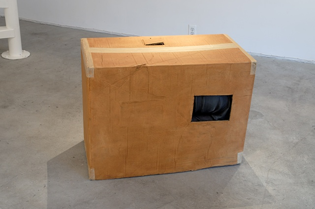 Figurative polychrome ultracal sculpture of adult man in cardboard box with cutouts