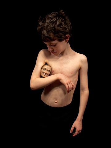 Digital C-print of a young boy with a small sculpted head under his arm