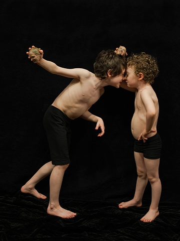 Digital C-prints of two boys, nose to nose,  holding tiny sculpted heads