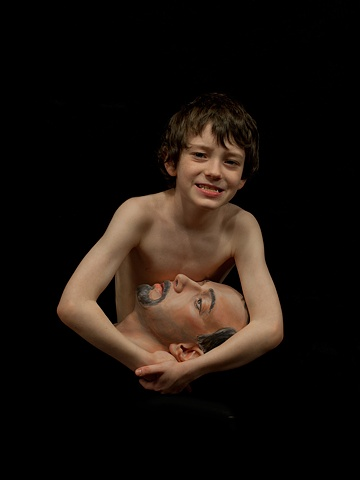 Digital C-prints of a boy on black background holding a sculpted man's head