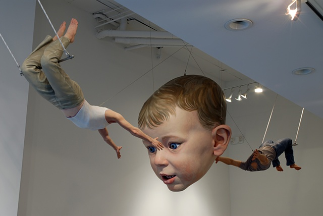 Figurative, polychrome sculpture of a life-size headless woman and man tossing a huge toddler's head between them on a trapeze