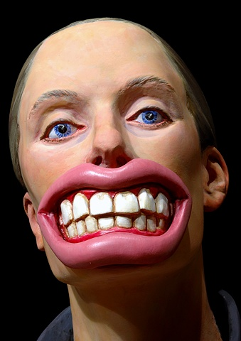detail of polychromes figurative sculpture of a woman wearing a mask of oversized teeth and lips